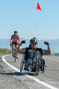 Athlete riding a recumbent handcycle flexes both arms in celebration of strength