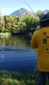 A man wearing a yellow shirt and hat holds a fishing pole and his line is being pulled. Across from him there are leafy green branches and a mountain in the distance.