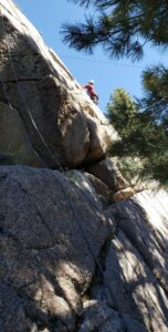 A rock climber is hardly visible climbing up a ginormous granite rock. A pine tree to the right of the image shades most of the rock, and two climbing ropes are visible hanging down the rock.