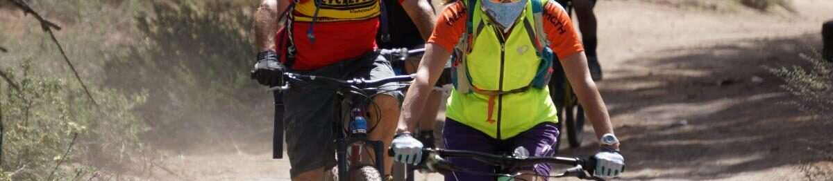 Multiple cyclists ride mountain bikes in a line.