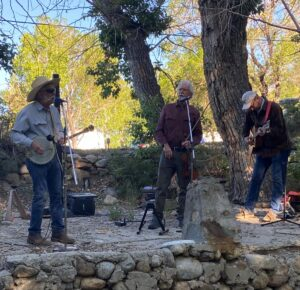 Three men are pictured standing on a stage made of rocks. The man on the left wears a cowyboy hat and plays the banjo while singing into a microphone. The man in the middle also sings into a microphone, and the man on the right plays the guitar.