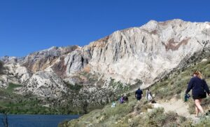 Hikers walk along a trail with a blue lake at the bottom left of the image and a towering mountain above them.