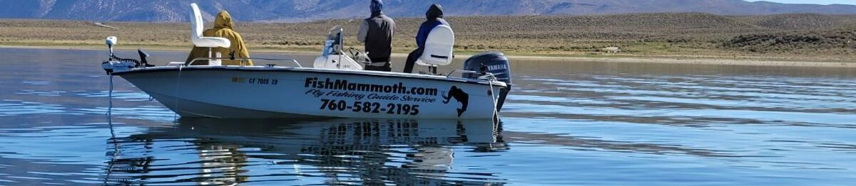 A boat with three individuals wait on top a glassy blue body of water. A wide mountain in across from them in the background of the image.